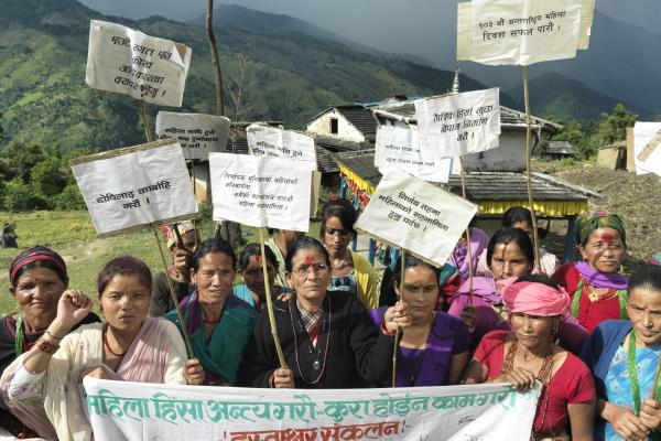A group of Nepali women hold a banner and placards as they protest in front of their remote village, with hills in the background