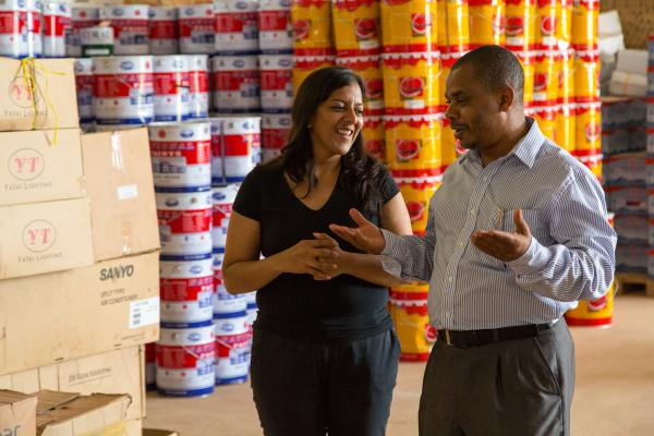A man and woman talk animatedly in a warehouse, in front of stacks of drums of produce