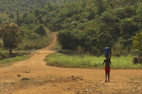 A boy carries water outside the village of Charlotte in Sierra Leone