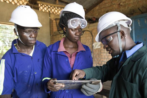 Whychliffe Rutalemwa, a Junior welding instructor with students, Tanzania
