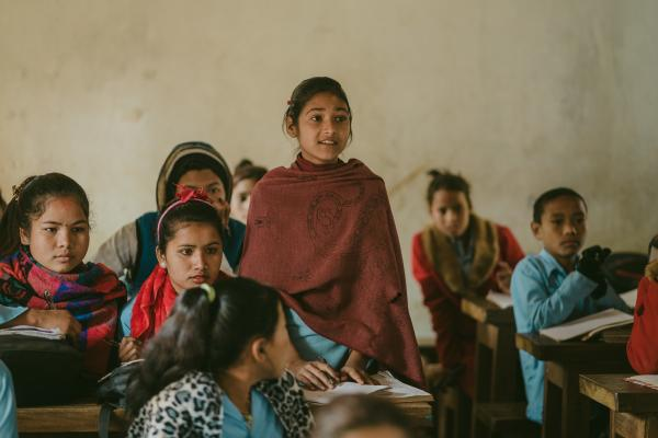 A girl stands up to speak in the classroom, surrounded by her classmates sitting at their desks.