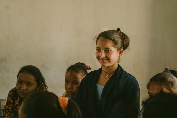 Nirmala smiles as she stands in the classroom, surrounded by her classmates who are sitting down