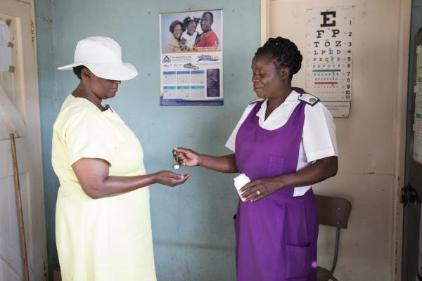 A nurse gives medication to a female inmate in the Chikurubi prison clinic