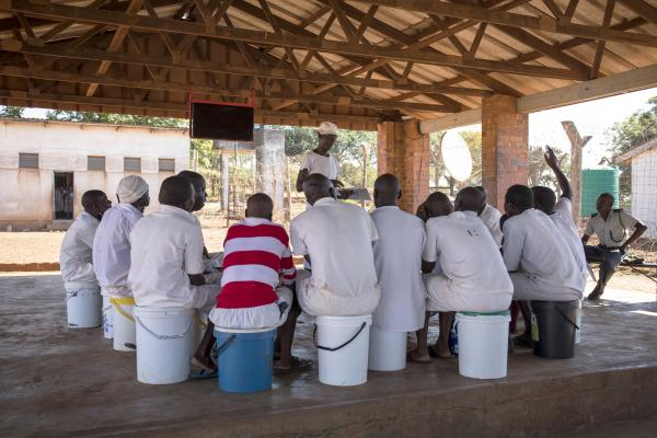 A group of male prisoners sit in a circle listening to a peer educator speak about health issues