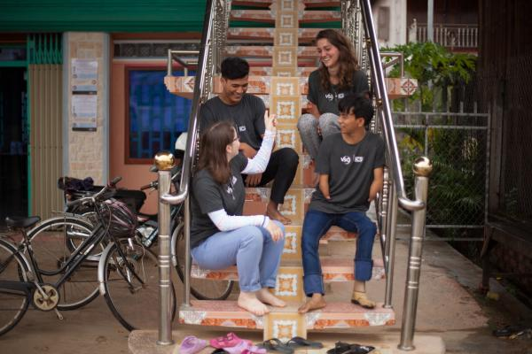 A group of four ICS volunteers laugh and talk together as they sit on a stairwell
