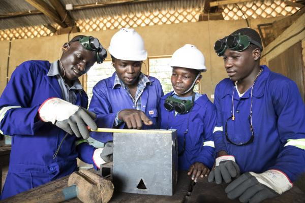 Four students dressed in overalls and safety wear gather around a metal box in a metalwork worshop
