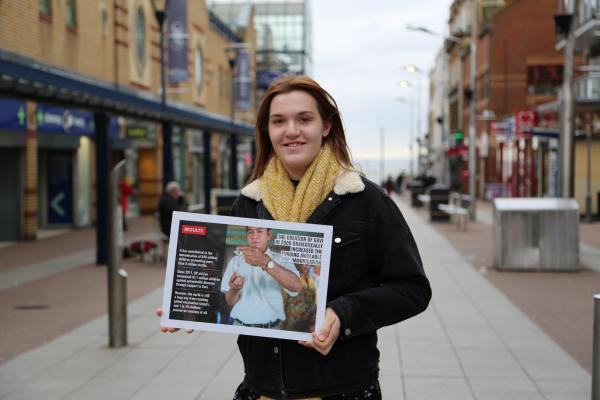 A young woman stands in a UK high street holding a poster which demonstrates the impact of campaigning for change