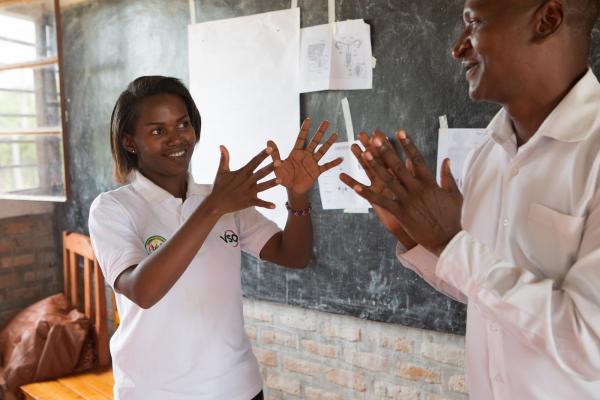 Volunteer Brown Niyonsaba signs with a fellow teacher in front of the blackboard, as part of a lesson on sexual and reproductive health