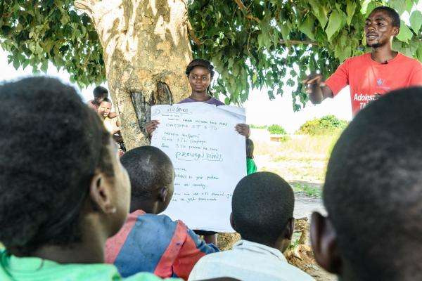 A young woman holds up a sheet of paper for a group, as Alfred delivers a peer education session
