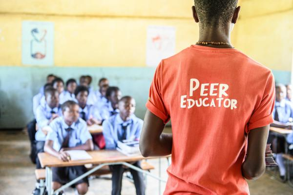 Peer educator Geofrey Mwaba stands at the front of a classroom to deliver a session