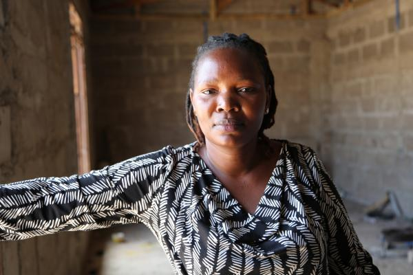 Felister Matoke Nyange stands in the staff accommodation she is building for her team of tailors