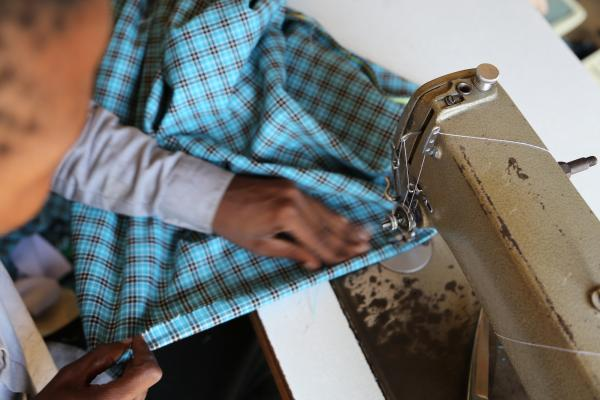 Close up of a tailor using a sewing machine