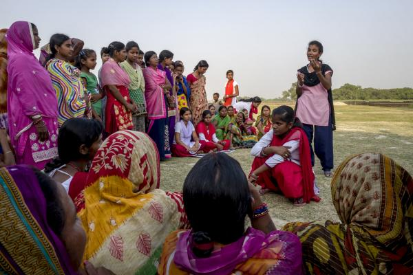 Women sit and stand in a semi-circle to watch two young women perform an interactive play about child marriage in Dobini, Nepal.