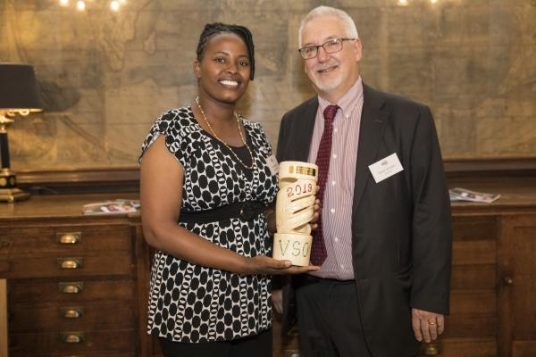Ann Wambu holds her 2019 Education Award and stands with Dave Kitchen of NASUWT