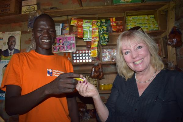 Sue with shopkeeper who has been able to expand his stock.