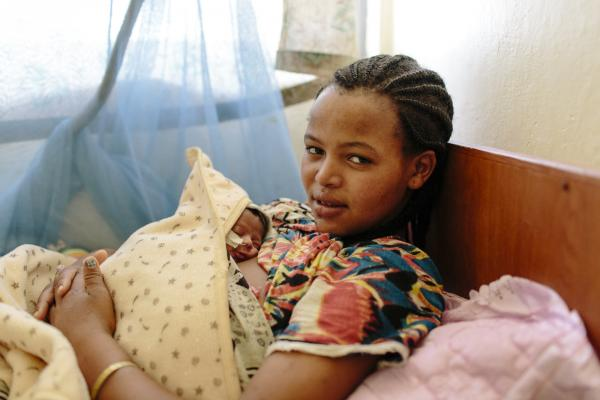 New mother Haimanot Haile rests as she holds her newborn baby against her chest