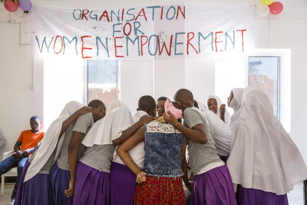 A group of girls huddle together under a sign reading 'Organisation for women empowerment'