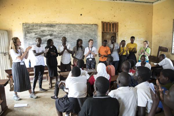 A group of ICS volunteers stands at the front of a school classroom, delivering a session on communication skills