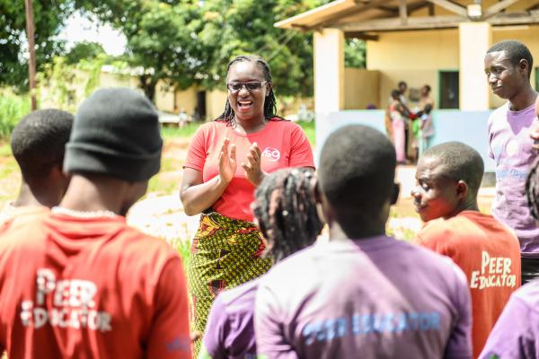 Volunteer Monica Atim talks to a group of peer educators she's trained
