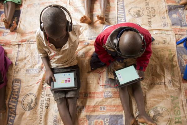 Two young schoolchildren sit on the floor at Mdzobwe Primary School and use their tablets to learn