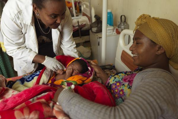 A mother smiles as she rests with her newborn baby, and a female doctor leans over to check on them
