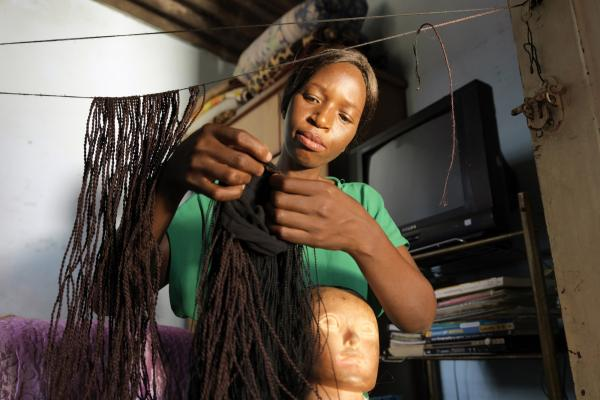 Merenciana, who learned her skills whilst in prison, braids hair at her home