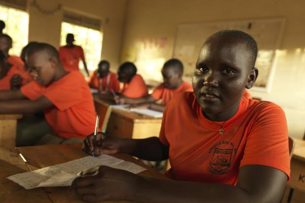 Student Stella works at her desk a the classroom at Kangole Girls' Secondary School, Moroto