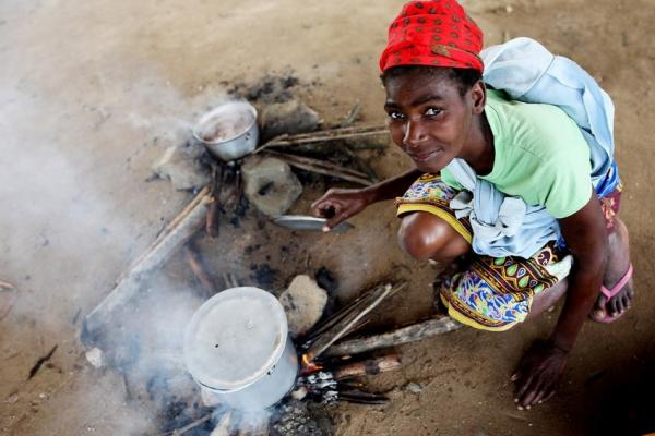 A young lady cooks on a fire in Mozambique