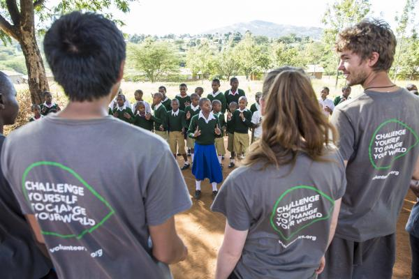 ICS volunteers watch and listen to a song performed by the pupils of Endagikot school