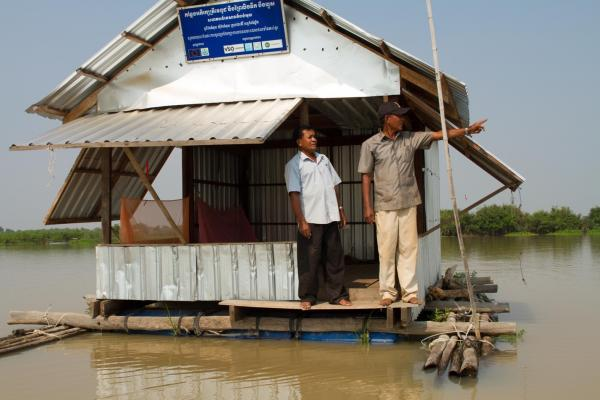 Two men stand on a small floating hut