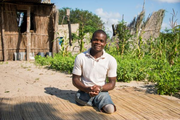Faife Mufundisse sits on a straw mat outside a partially-destroyed house in Chimoio, Mozambique