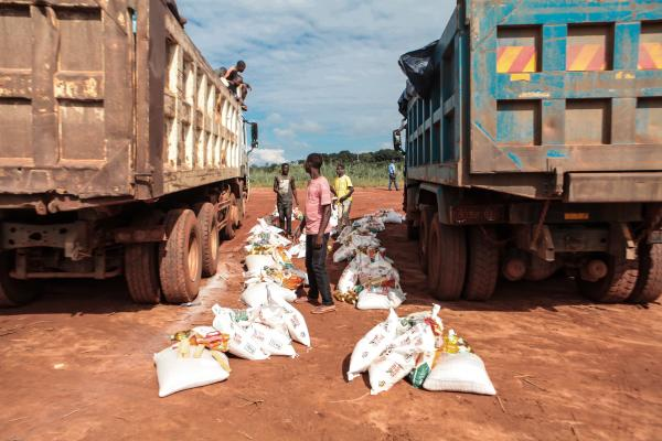 Volunteers unload sacks of food from two large trucks VSo/in Manjacure, Manica province.