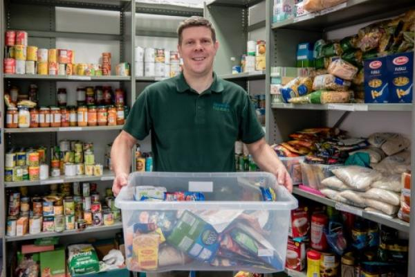 Man in foodbank holding donated items