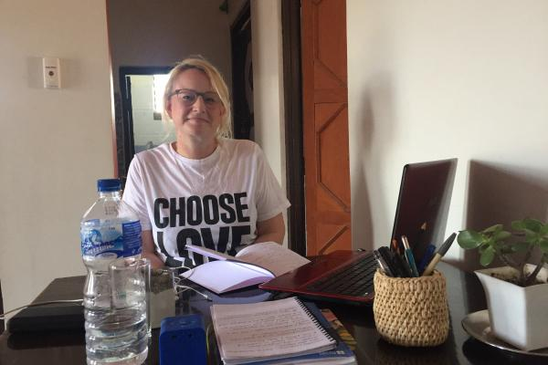 Nicola Whybrow sits at a desk on her laptop, as she works out of her placement accommodation in Nepal.