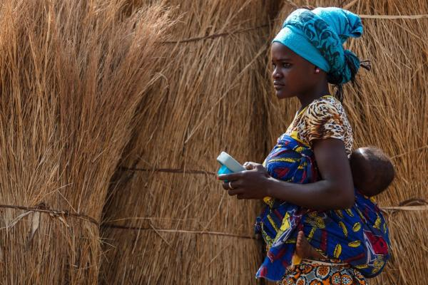 A young mother with her baby on her back uses an Amplio Talking Book in Ghana