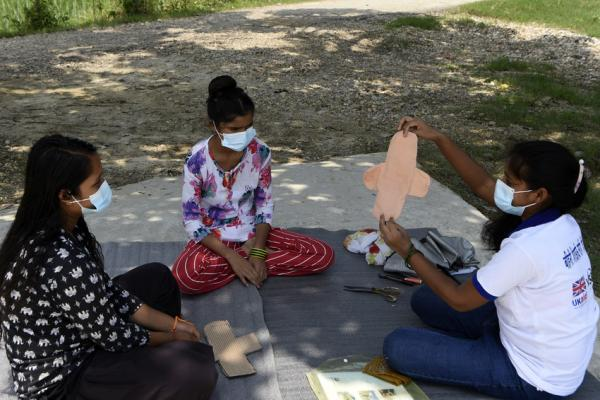 three woman sat on the floor outside. One is teaching how to make a reusable sanitary pad