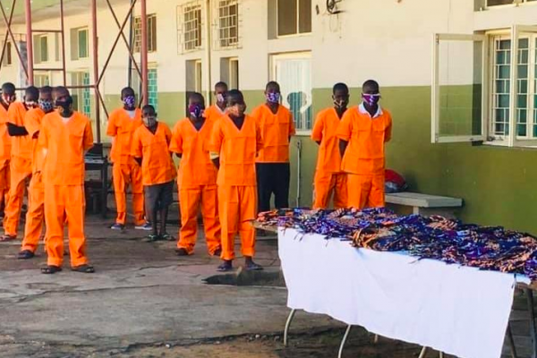 A group of prisoners in orange jumpsuits wearing masks