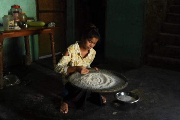 A young girl sits on a low stool in her family's home, examining a large dish of rice as part of dinner preparations