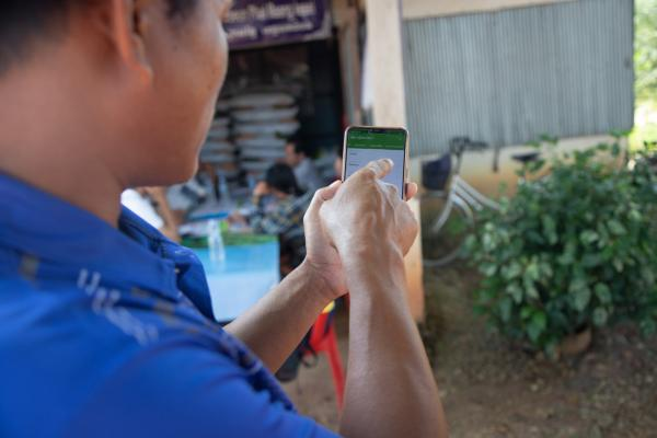 A lead farmer on the Improving Market Access for the Poor project uses a mobile phone app