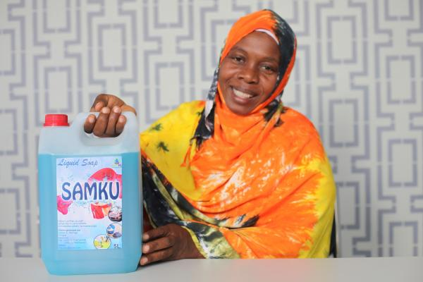 A woman smiles as she proudly shows a large bottle of liquid soap