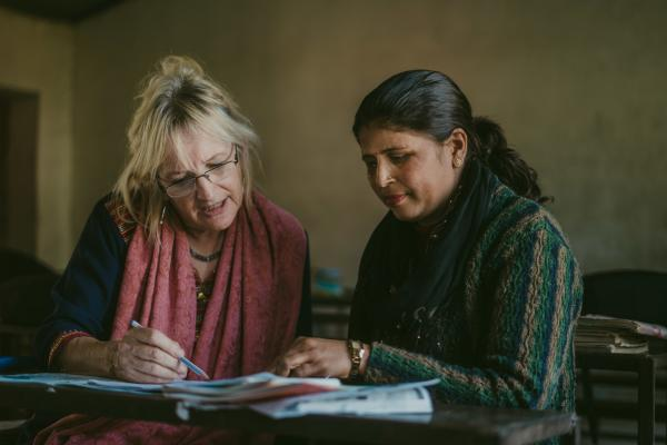 Volunteer Anne and a local schoolteacher sit at a classroom desk, looking at students' work together
