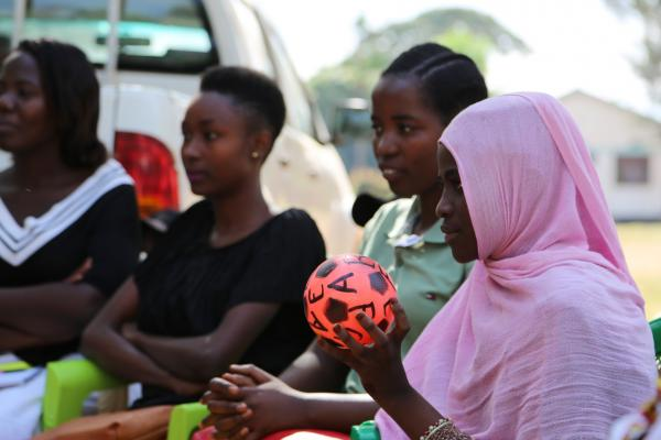 Jida, a young woman, holds a small football as part of a warm-up exercise in an aspirations analysis session