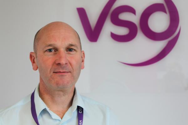 VSO Chief Executive Philip Goodwin in front of the VSO logo