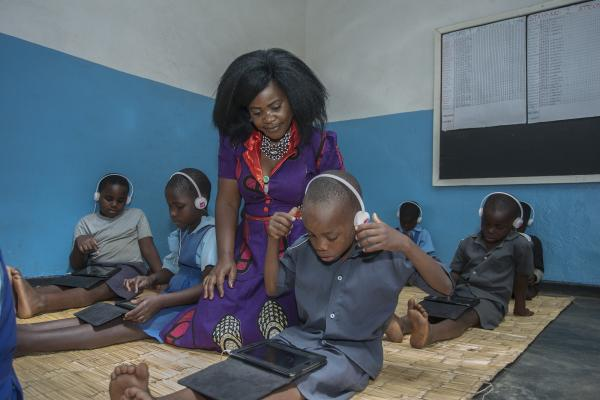 Teacher Grace monitors children using Unlocking Talent digital education technology