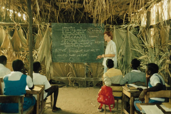 Man stood in the front of a rural classroom, giving a lesson to students in the Gambia