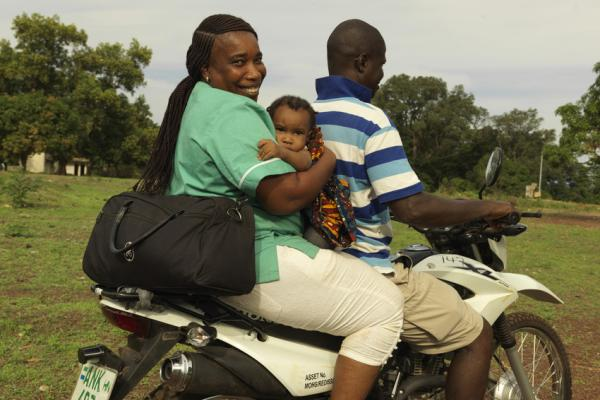 Midwife Catherine Swaray carries her own baby to work everyday on the back of a motor bike