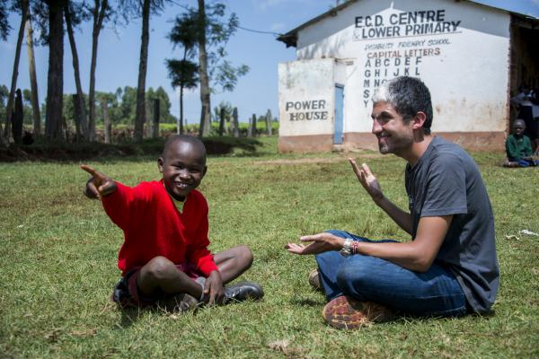 ICS volunteer Asher sits next to a deaf primary school student