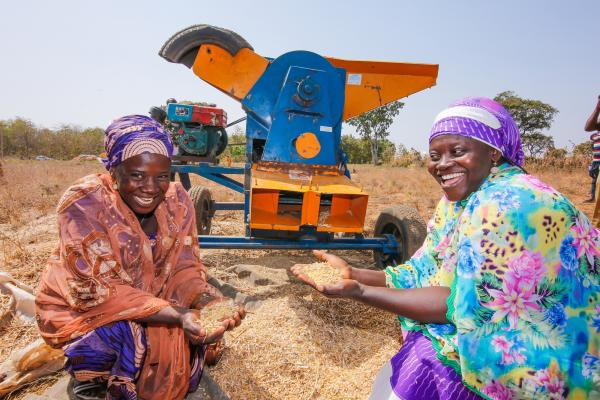 Fatima Zubairu and Fatima Al Hassan are pictured here with a thresher machine that strips the husks and stalks from soya beans.