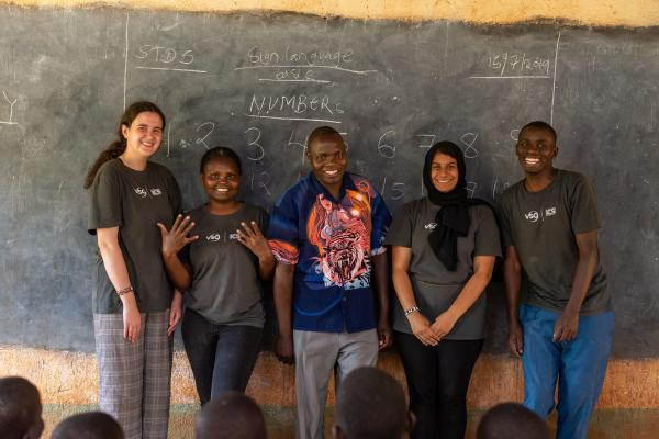 four volunteer standing at the front of a classroom, smiling at the camera
