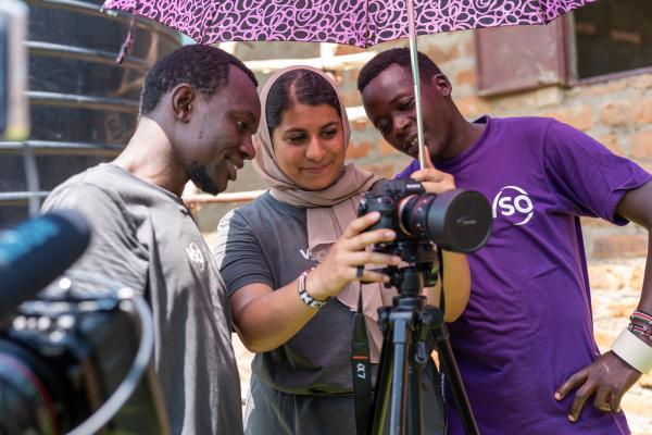 two boys stood either side of a female volunteer who is holding a video camera and recording